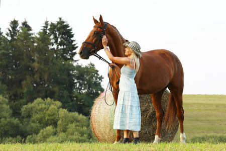 Romantic scene with woman caressing her horse