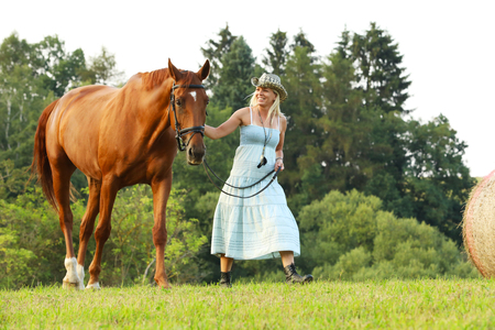 Woman in blue dress lead chestnut horse through meadow Stock Photo