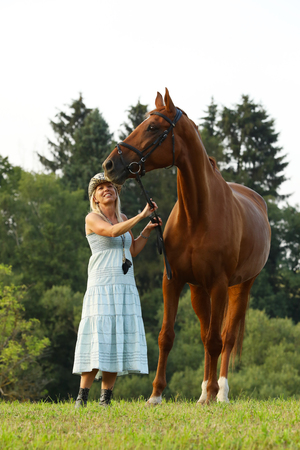 Portrait of woman and her chestnut horse Stock Photo