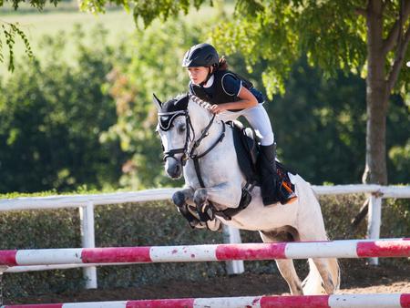 Mädchen mit weißem Pony, das über die Hürde auf Pferdewettbewerb springt Standard-Bild