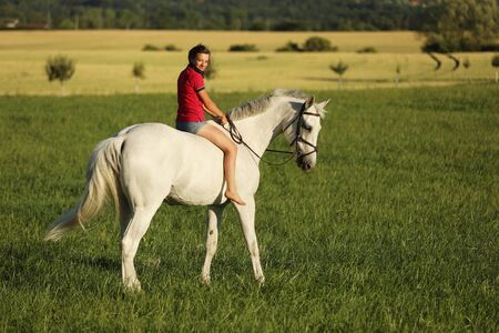 Young girl ride on white horse without saddle on meadow in late afternoon, sunset time