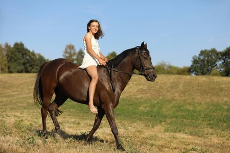 Happy teenage pretty girl on pony without saddle running on meadow in hot summer afternoon Stock fotó - 135497655