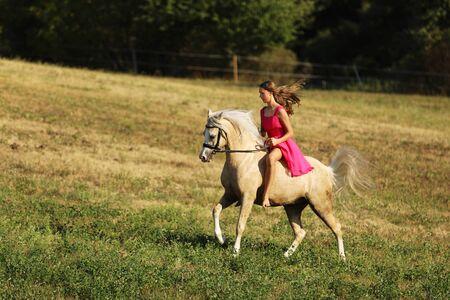 Teenager-Mädchen galoppieren auf Pony ohne Sattel auf der Wiese am sonnigen Sommernachmittag Standard-Bild