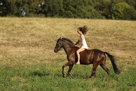 Young girl in white dress running on horse without saddle through meadow on summer afternoon