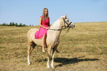 Teen girl on palomino ponny in pink dress without saddle in sunny afternoon