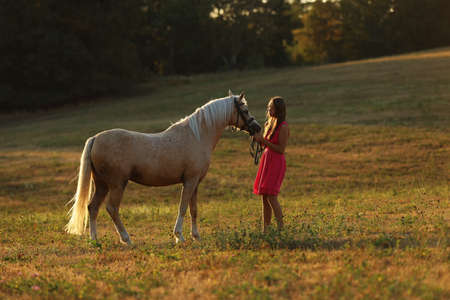 Romantic scene with teen girl and her pony on meadow in summer sunset. Face to face