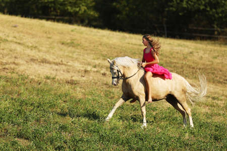 Young girl in pink dress galloping on ponny on meadow in summer afternoon