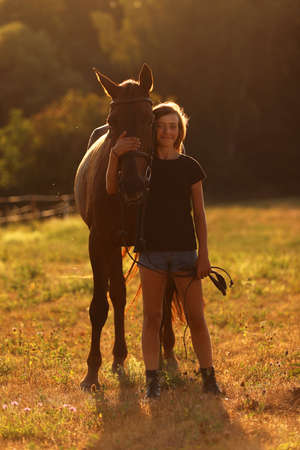Young girl with chestnut horse on meadow during summer sunset. Romanic scene