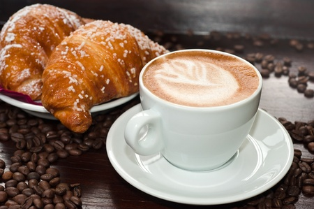 coffee and cake: Cappuccino and croissant with coffee beans Stock Photo