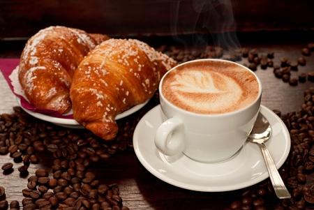 capuchino: Cappuccino y un croissant con granos de caf� Foto de archivo