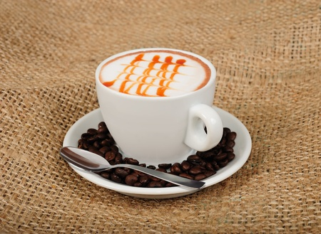 Cappuccino with coffee beans and teaspoon photo