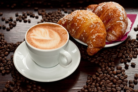 Cappuccino and croissant with coffee beans photo