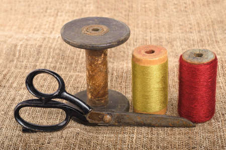 old spools: Scissors and spools  on canvas background