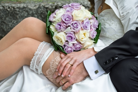 Married couple with rings, garter and bouquet photo