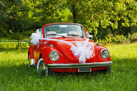 Red wedding car with white ribbon Stock Photo