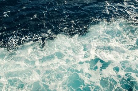 Blauwe zee met golven en schuim Stockfoto
