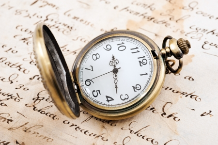 Vintage pocket watch over manuscript photo