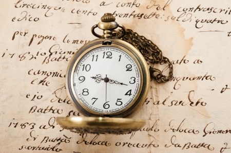 count down: Vintage pocket watch over manuscript