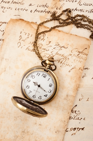 watch over: Vintage pocket watch over manuscript background