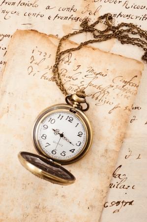 watch over: Vintage pocket watch over manuscript background