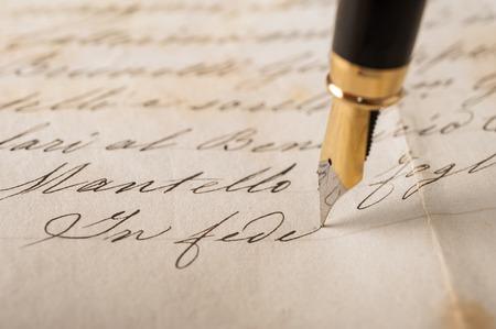 pluma de escribir antigua: Pluma fuente escrito en una vieja carta manuscrita