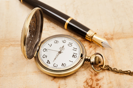 pocketwatch: fountain pen and pocketwatch on old parchment Stock Photo