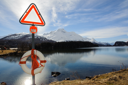 cautions: lifebuoy and ban the signboard in front of an alpine lake
