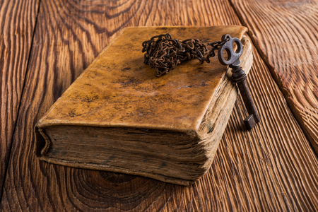 passkey: Old key with chain on an book