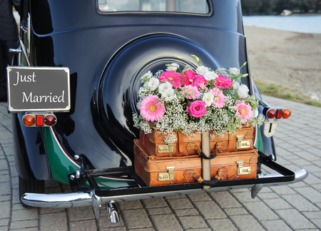 Wedding bouquet on vintage wedding car Foto de archivo