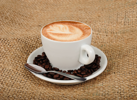 capuccino: Cappuccino with coffee beans on jute background Stock Photo