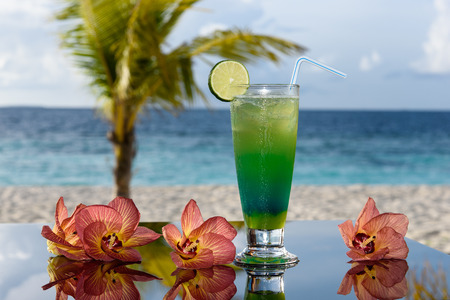 Green cocktail with flowers in a beach