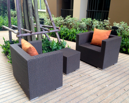 Outdoor wood sofa with orange pillows in the garden