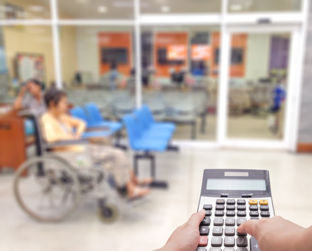 Medical expense concept by the calculator with blur patient at the hospital in background 版權商用圖片