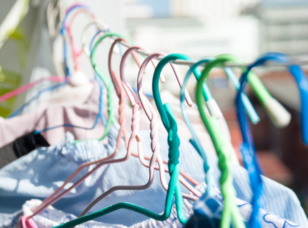Colored coat hanging to the rope with green background Stock Photo
