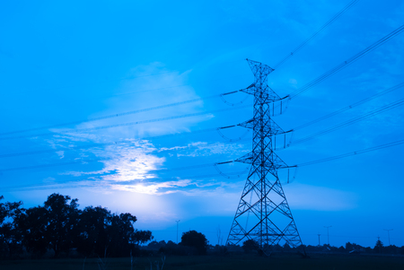 electric grid: The electric post in the night and trees in background Stock Photo