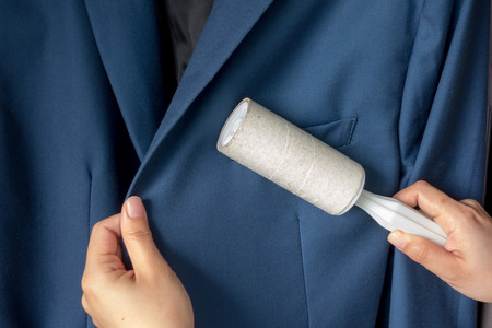 dry suit: Dry cleaning and business theme: a man hand with blue suit holding a white sticky brush for cleaning clothes and furniture from dust