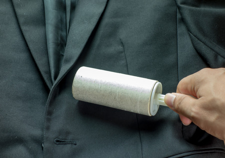 dry suit: Dry cleaning and business theme: a man hand with black suit holding a white sticky brush for cleaning clothes and furniture from dust