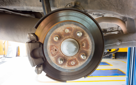 removed: Rear disc brake on car in process of new tire replacement. The rim is removed showing the rear rotor and caliper