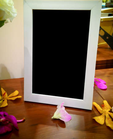 orchid house: Blank photo frame on the wood table with orchid flower,digital effect vintage style