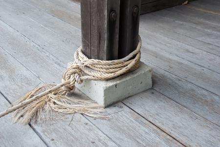mooring bollard: Mooring bollard with nautical rope knotted on it