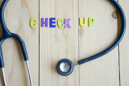 doctor burnout: Health check up text with stethoscope on wood table