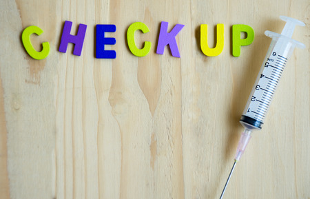 doctor burnout: Health check up text with syringe on wood table