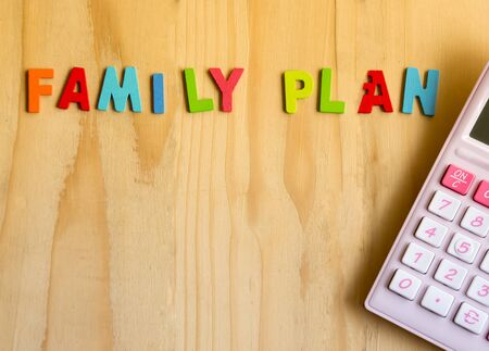 young family: Family planning text with pink calculator on wood table background