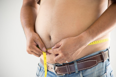 paunch: Overweight man wearing jeans measuring her fat body belly paunch
