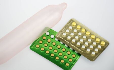 birth control: The pink condom and birth control pill on white brackground Stock Photo