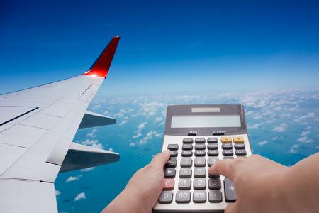 電卓とバック グラウンドで飛行機による旅行費用計算の概念