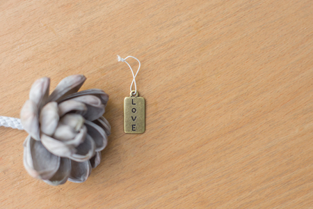 The love tag with white flower on wood table