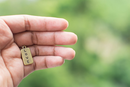 The love tag in mans hand with tree in background