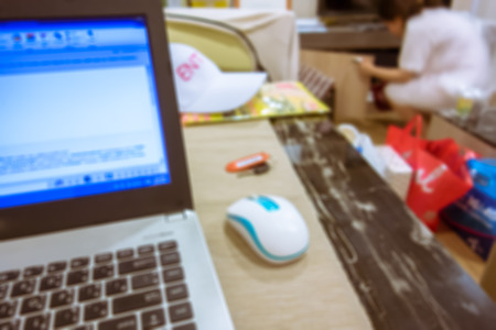 The blur of laptop on desk and young girl in background 版權商用圖片 - 62060051