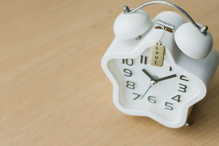Top view close up of white clock on the wood table